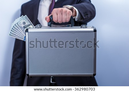 Man in suit holds metal briefcase with dollars - stock photo