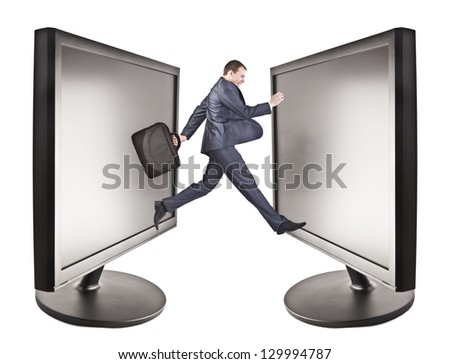 man in suit is jumping into computer screen two pc monitor stand opposite each other - stock photo