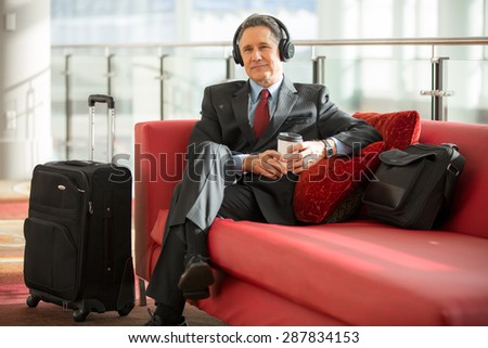 Man in suit is patiently waiting in airport terminal - stock photo