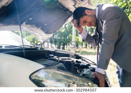 Man in suit looking under the hood of breakdown car outdoors - stock photo