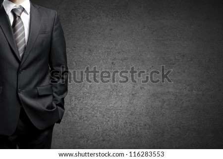 man in suit on a concrete wall background - stock photo