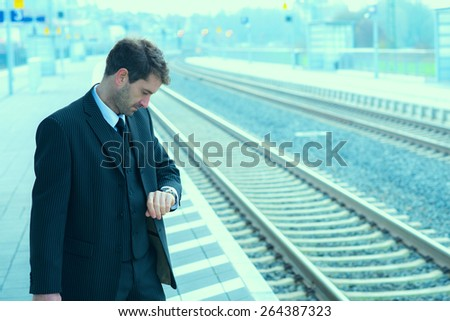 man in suit on business trip is looking on his watch  - stock photo
