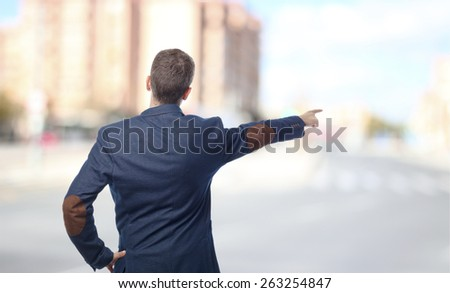Man in suit pointing back in a city - stock photo