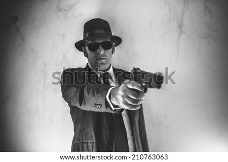 Man in Suit Points Gun. Man in suit, hat and sunglasses points a gun. - stock photo