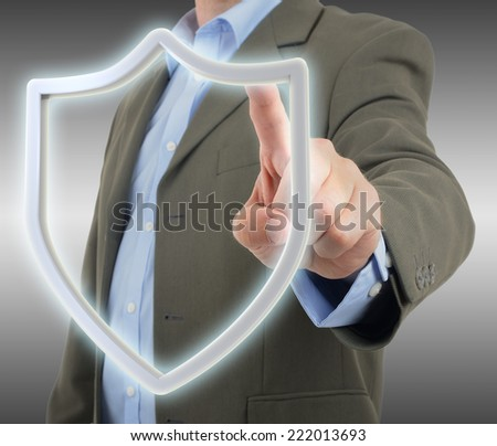 Man in suit pressing a security shield icon on a virtual screen - stock photo