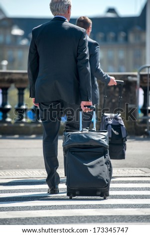 Man in suit pulling travelling suitcase on the street - stock photo