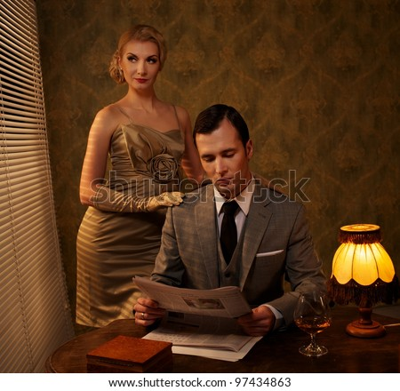 Man in suit reading newspaper with woman behind him. - stock photo