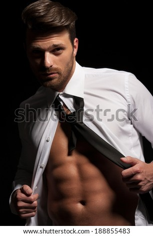 Man in suit showing abs a result of hard workout, muscular body, white shirt and tie - stock photo