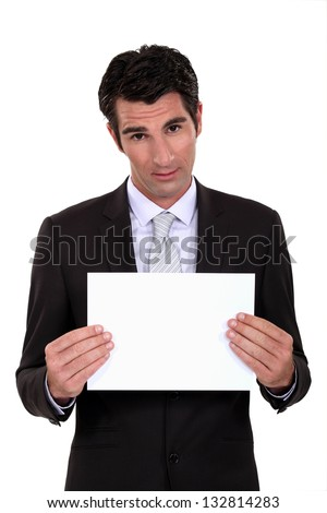Man in suit showing blank sheet of paper - stock photo