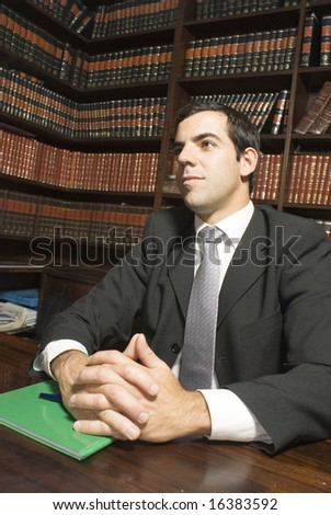Man in suit sits at desk with hands folded. There are books in the background. Vertically framed photo. - stock photo