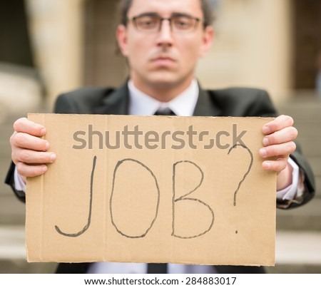 Man in suit sitting at stairs with sign in hands. Unemployed man looking for job. - stock photo