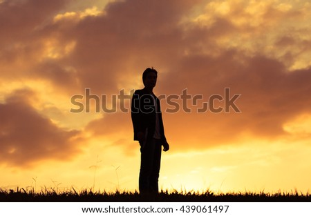 Man in suit standing in a open field.  - stock photo