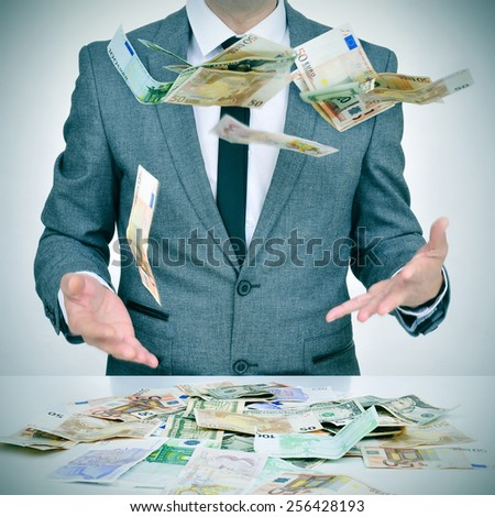 man in suit trying to catch money falling from the sky - stock photo