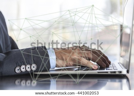 Man in suit using laptop in office - stock photo