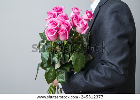 Man in suit with bouquet of roses. Pink flowers on a gray background - stock photo