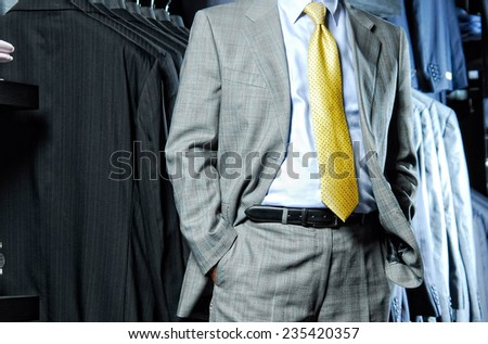 Man in suit with hands in pockets. - stock photo