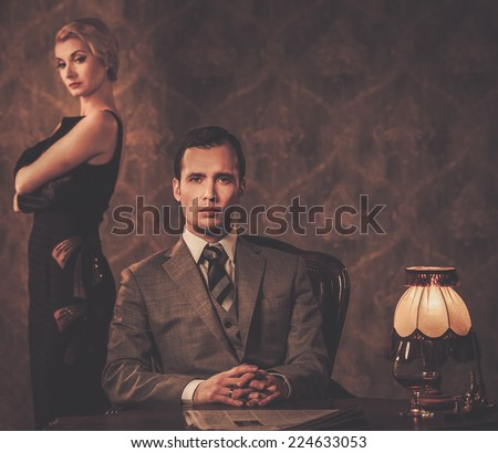 Man in suit with woman behind him - stock photo