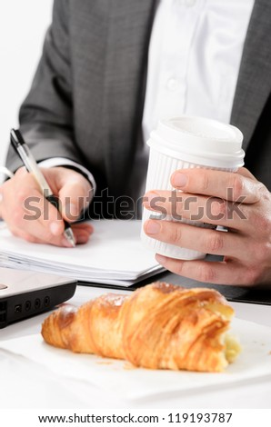 Man in suit writes while having a breakfast croissant and drinks coffee - stock photo
