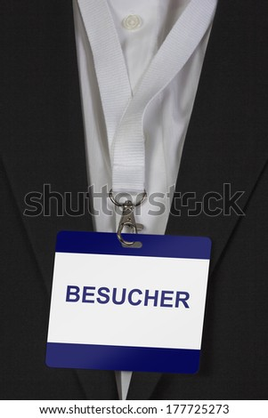 """man in suite wearing a pass labeled """"Besucher"""" (German Visitor) arround his neck - stock photo"""