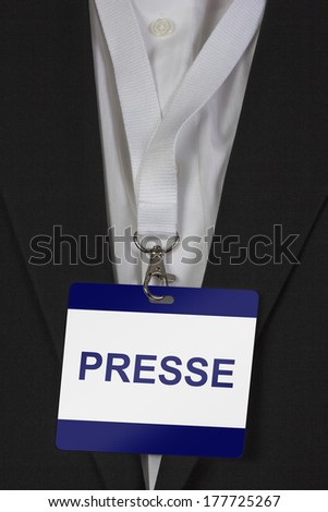 """man in suite wearing a pass labeled """"Presse"""" (German Press) arround his neck - stock photo"""
