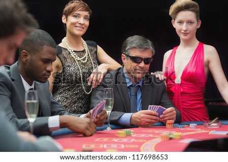 Man in sunglasses playing poker with two women either side in casino - stock photo