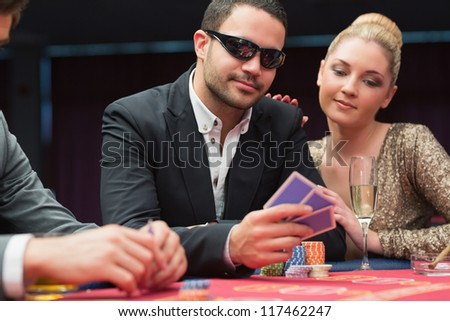 Man in sunglasses showing hand to woman beside him at poker game in casino - stock photo