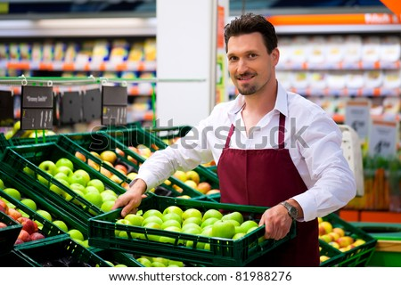 Man in supermarket as shop assistant; he brings some boxes with apples - stock photo