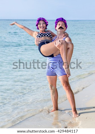 Man in swimsuit holding in his arms woman in swimsuit on the sea beach. A pair of retro swimwear standing on coast. Happy couple in vintage style swim dress with bathing cap relax by the sea. - stock photo