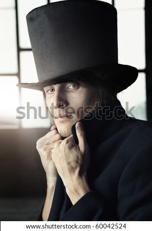 Man in the black coat and top hat - stock photo