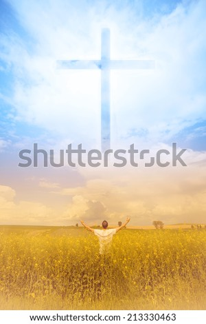 Man in the field worshiping God and the symbol of the Cross that appears in the sky - stock photo