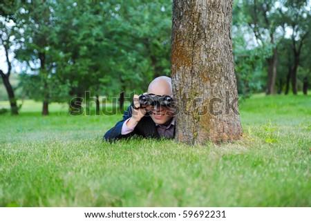 man in the green park looking through binoculars - stock photo