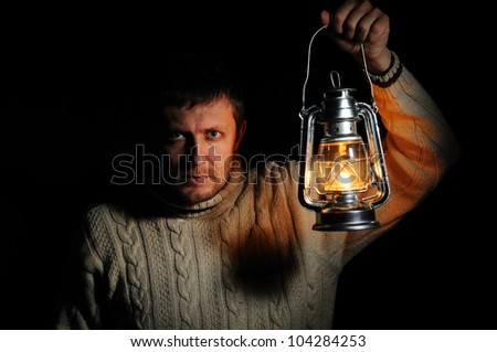 Man in the night with a burning kerosene lamp on black background, concept - stock photo