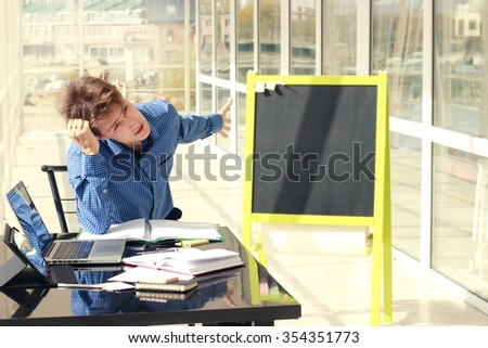 Man in the office or class room try to find problem solution.  Teacher in the classroom in front of the chalkboard.  - stock photo