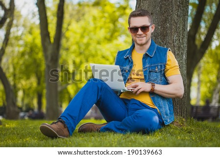 man in the park sitting on the grass with a laptop - stock photo