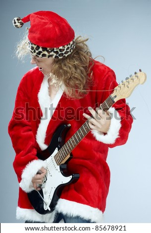 Man in the red and furry Santa Claus costume playing rock guitar - stock photo
