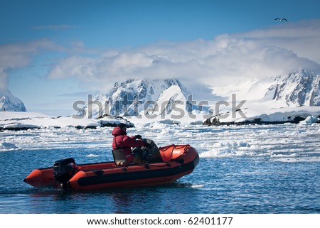man in the red boat in Antarctic waters - stock photo