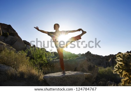 Man in the yoga pose Utthita Hasta Padangustasana (Extended Hand-To-Big-Toe Pose) while balanced in a desert landscape with the sun bursting through his core. - stock photo