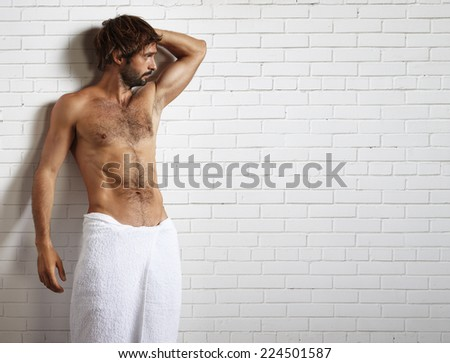 man in towel and brick wall behind - stock photo
