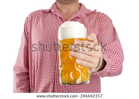 Man in traditional Bavarian shirt holds mug of beer in front of a white background - stock photo