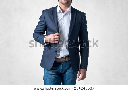 Man in trendy suit  standing alone holding his jacket with confidence. - stock photo