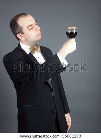 Man in tuxedo looking at the glass filled with red wine. - stock photo