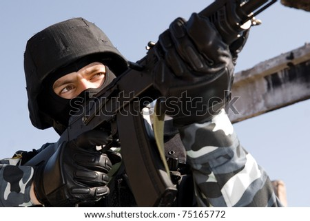 Man in uniform and bulletproof helmet targeting with russian AK-47 rifle - stock photo