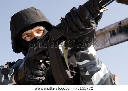 Man in uniform and bulletproof helmet targeting with russian AK-47 rifle - stock photo