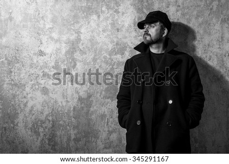 man in vintage cap and coat standing near old wall. black and white photo - stock photo