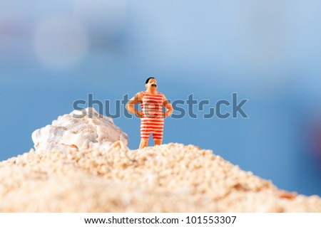 Man in vintage swimming costume standing on the beach - stock photo
