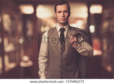 Man in waistcoat with jacket over his shoulder against blurred background - stock photo