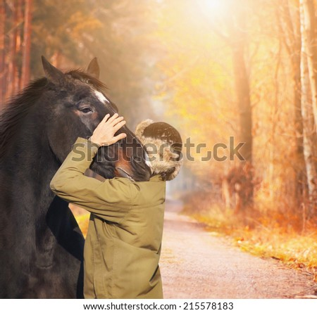 Man in warm jacket and fur hat hug  horse on  background of autumn forest - stock photo
