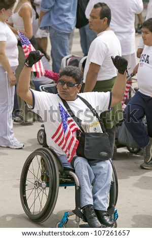 Man in wheel chair holds US flag in sympathy with immigrants participating in march for Immigrants and Mexicans protesting Illegal Immigration reform by U.S. Congress, Los Angeles, CA, May 1, 2006 - stock photo