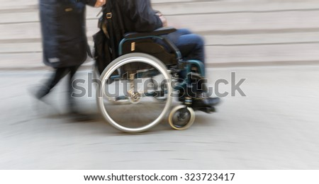 Man in wheelchair pushed by woman in blurred motion - stock photo