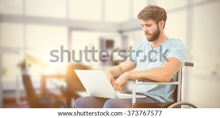 Man in wheelchair using computer against board room - stock photo